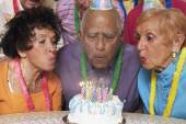 Senior Mixed Race man blowing out birthday candles — Stock Photo