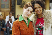 Multi-ethnic women hugging with friends in background — Foto Stock