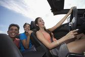 Multi-ethnic friends driving in convertible — Stock fotografie