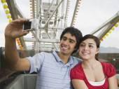 Multi-ethnic teenaged couple on carnival ride — Stock Photo