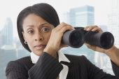 African businesswoman holding binoculars — Stock Photo