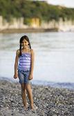 Mixed Race girl standing on rocky beach — Stock Photo
