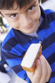 Hispanic boy holding bread and cheese — Stock Photo