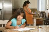 Hispanic girl coloring in kitchen — Stock Photo