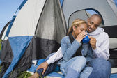 African couple drinking coffee at campsite — Stock Photo