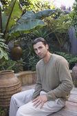 Hispanic man sitting in garden — Stock Photo