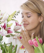 Hispanic woman smelling flowers — Stock Photo