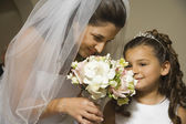 Hispanic bride and young girl smelling flowers — Stock Photo