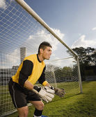 Hispanic male soccer player blocking goal — Stock Photo