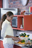 African American woman chopping vegetables — Stock Photo