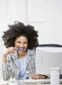 African American businesswoman biting on pen — Stok fotoğraf