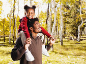 African father holding daughter on shoulders — Stock Photo