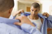 Hispanic man putting on shirt — Stock Photo
