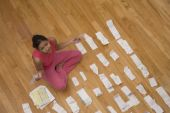 Hispanic woman surrounded by receipts — Stock Photo