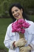 Hispanic woman holding flowers — Stock Photo