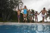 Multi-ethnic family jumping into swimming pool — Stock Photo