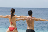 Multi-ethnic couple practicing yoga at beach — 图库照片