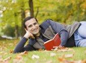 Hispanic man reading in grass — Stock Photo