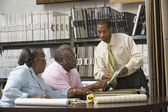 African American couple looking at flooring samples — Foto Stock