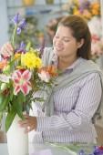 Hispanic female florist arranging flowers — Stock Photo