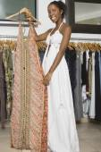 African woman holding dress in clothing store — Stock Photo