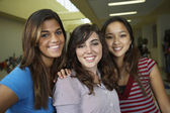 Multi-ethnic teenaged girls hugging in school hallway — Stock Photo
