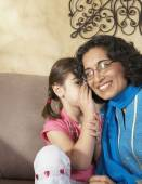 Middle Eastern girl telling grandmother a secret — Stock Photo