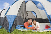 Hispanic couple looking at laptop in tent — Stock Photo