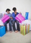 African twin sisters looking in shopping bags — Stock Photo