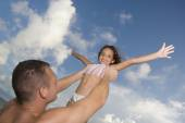 Father holding daughter in air — Stock Photo