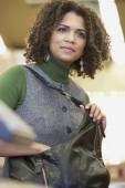 African woman reaching in purse — Stock Photo