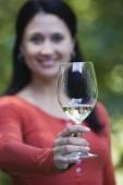 Hispanic woman holding up wine glass — Stock Photo
