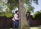 African couple peeking around tree — Stock Photo