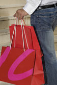 Hispanic woman holding shopping bags — Stock Photo