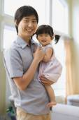Asian father holding baby daughter — Stock Photo