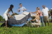 Multi-ethnic friends setting up tent — Stock Photo