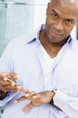 African American man clipping fingernails — Stock Photo