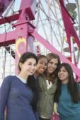 Multi-ethnic girls in front of Ferris wheel — Stock Photo