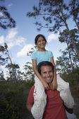 Hispanic man holding daughter on shoulders — Stock Photo