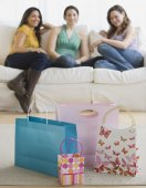 Three young women looking at gift bags — Stock Photo