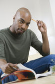African American man reading text book — Stock Photo