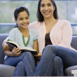 Mixed Race mother and daughter reading — Stock Photo #52070311