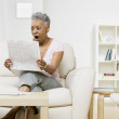 Senior African American woman reading newspaper — Stock Photo #52070627