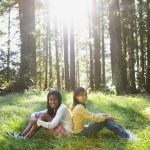 Multi-ethnic girls sitting in woods — Stock Photo #52070755