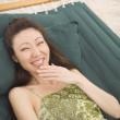 Asian woman laughing in hammock — Stock Photo #52070899