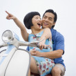 Asian couple riding motor scooter — Stock Photo #52071029