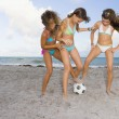 Multi-ethnic girls playing soccer at beach — Stock Photo #52071353