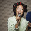 Asian woman in curlers singing — Stock Photo #52071527