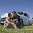 Hispanic couple in front of low rider car — Stockfoto #52072457