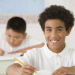 Hispanic boy writing at school desk — Stock Photo #52072723